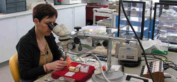 Photo: André Bergeron, Centre de conservation du Québec. Une restauratrice effectue une intervention délicate sur un objet archéologique.
